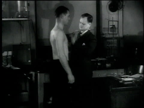 vídeos de stock e filmes b-roll de 1930s montage doctor taps on the bare chest of a patient, then listens to chest with stethoscope / washington d.c., united states - estetoscópio
