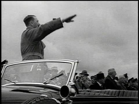 1930s MONTAGE Hitler standing in a car and saluting as trucks full of civilians and soldiers drive past in review / Germany