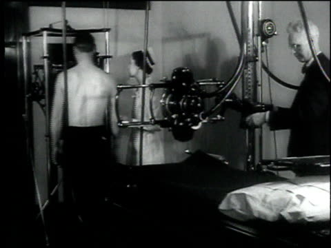 stockvideo's en b-roll-footage met 1930s montage nurse helps patient ready himself for x-ray machine to check his lungs / washington d.c., united states - medische röntgenfoto