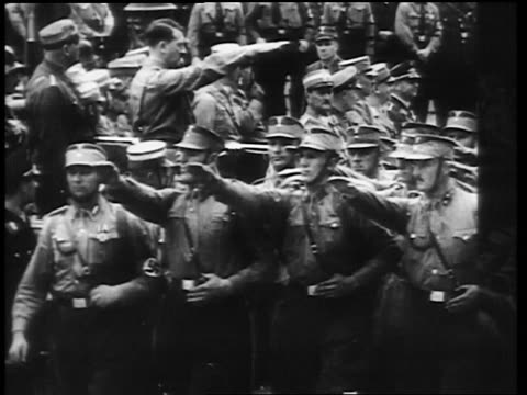 b/w 1930s nazis in uniforms marching past adolf hitler and saluting - 1930 stock-videos und b-roll-filmmaterial