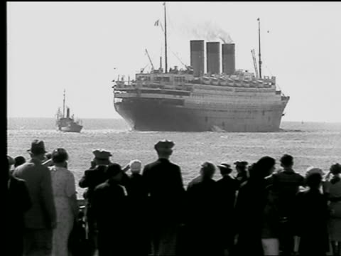 b/w 1930s ocean liner leaving harbor / people watching in foreground / le havre, france - normandie stock-videos und b-roll-filmmaterial