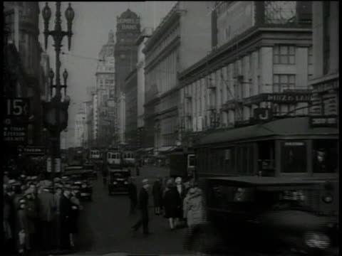 1930s ws pedestrians, automobiles, and cable cars on a san francisco street / california, united states - san francisco california stock-videos und b-roll-filmmaterial
