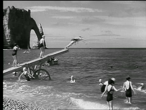 B/W 1930s people jumping off board into ocean + swimming / cliffs in background / Etretat, Normandy, France