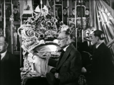 b/w 1930s people put offerings in statue in buddhist temple at chinese new year / man in mask in background - buddhismus stock-videos und b-roll-filmmaterial