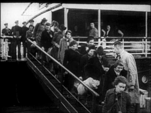 stockvideo's en b-roll-footage met b/w 1930s people walking down gangplank of ship / refugees fleeing germany after hitler's takeover - vluchteling ontheemden