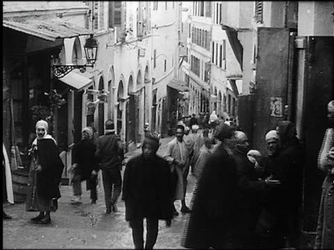 b/w 1930s people walking on narrow hilly street in casbah quarter / algiers, algeria - アルジェリア点の映像素材/bロール