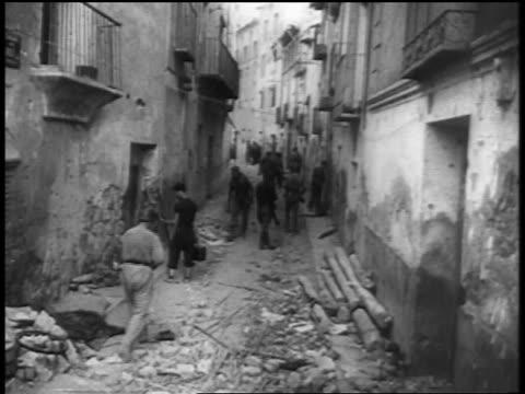vidéos et rushes de 1930s people walking on rubble covered narrow street / spanish civil war - guerre civile