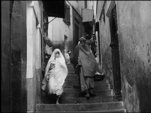 b/w 1930s people walking up + muslim woman walking down narrow stairway in casbah / algiers - アルジェリア点の映像素材/bロール