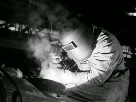 B/W 1930s person welding in factory / documentary