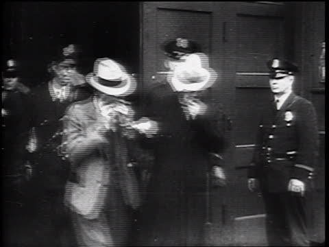 B/W 1930s police escorting men with handcuffs from building