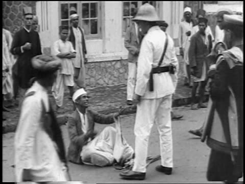 B/W 1930s policeman menacing antiBritish protester on ground in demonstration / New Delhi India
