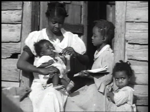 1930s ms poor mother with children sitting outside house / united states - archival stock videos & royalty-free footage