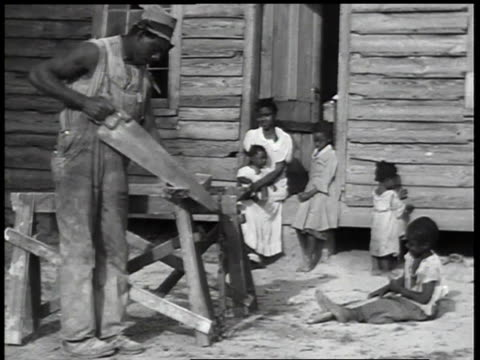 1930s ws poor sharecropper family outside house watching worker sawing wood / united states - poor family stock videos & royalty-free footage