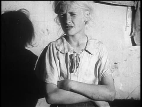 b/w 1930s portrait blonde girl with folded arms standing near truck chewing gum / homless families - una ragazza adolescente video stock e b–roll