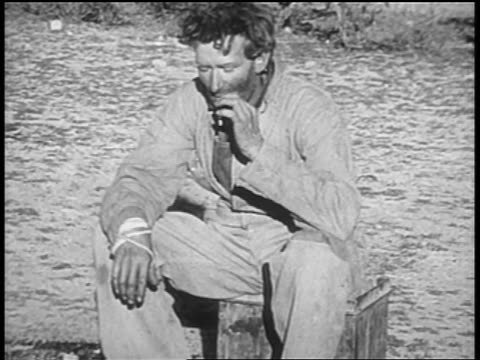 1930s portrait man sitting on box outside smoking / homless dust bowl families - stoppelbart stock-videos und b-roll-filmmaterial