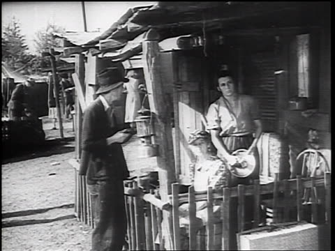vidéos et rushes de b/w 1930s portrait man woman on porch of shantytown shack looking at camera - la grande dépression