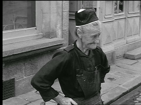 b/w 1930s ms portrait senior woman in hat talking on sidewalk / brittany, france - ブルターニュ点の映像素材/bロール
