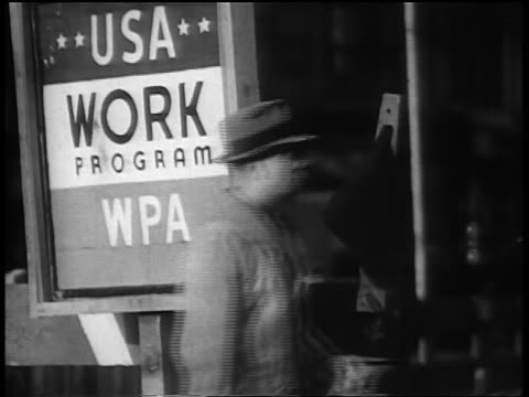 b/w 1930s profile two men walking past wpa sign on building during great depression - new deal video stock e b–roll