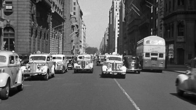 vídeos de stock e filmes b-roll de b/w 1930s rear car point of view driving + parking on 5th avenue with traffic + buildings / new york city - 1930