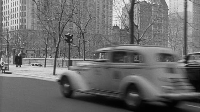 b/w 1930s rear car point of view on 5th avenue with central park + plaza hotel in background / new york city - 1930 stock videos and b-roll footage