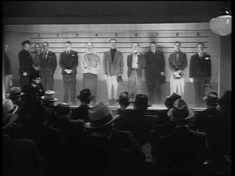 B/W 1930s REAR VIEW audience in foreground looking at police lineup / policeman taps two men on shoulders