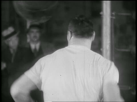 b/w 1930s rear view boxer hitting punching bag in gym - primo carnera stock videos and b-roll footage