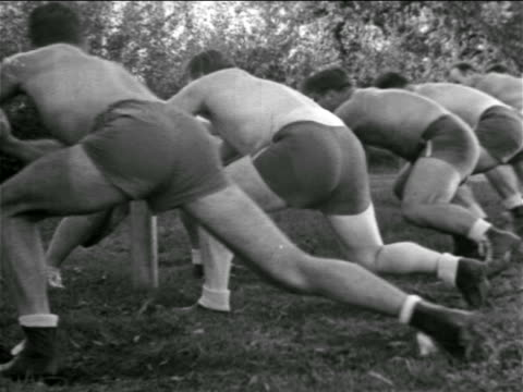 b/w 1930s rear view line of shirtless football players practicing at blocking posts - shirtless stock videos & royalty-free footage
