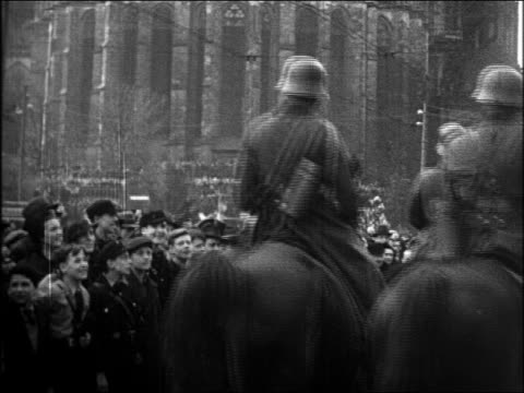 1930s rear view nazi soldiers riding horses in parade with people saltuing / rhineland - erbivoro video stock e b–roll