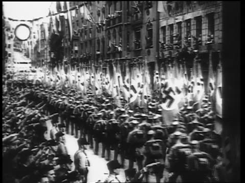 b/w 1930s rear view nazis marching in parade carrying flags with swastikas - hakenkreuzfahne stock-videos und b-roll-filmmaterial