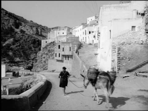 1930s REAR VIEW woman leading donkey carrying baskets on village road / Spain