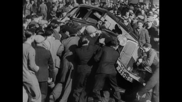 1930s riots on the streets of france and belgium with men running in the streets and cars being overturned - 1930 stock-videos und b-roll-filmmaterial