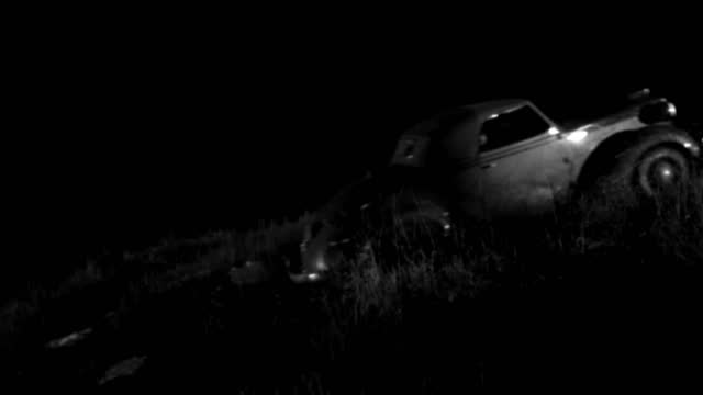 a 1930s roadster drives up onto a grassy hill at night. - 1930 1939 stock-videos und b-roll-filmmaterial