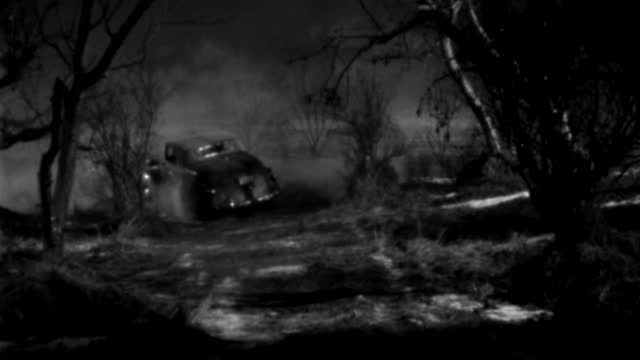 a 1930s roadster travels on a dark, misty road at night. - 1930 1939点の映像素材/bロール
