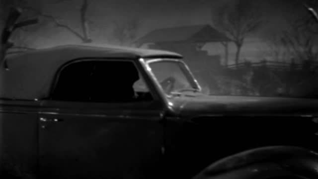a 1930s roadster travels through a misty farm at night. - 1930 1939点の映像素材/bロール