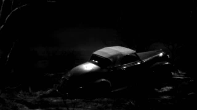 a 1930s roadster travels through misty woods at night. - 1930 1939点の映像素材/bロール