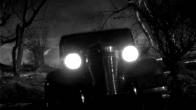 a 1930s roadster turns down a dark, misty path at night. - 1930 1939点の映像素材/bロール