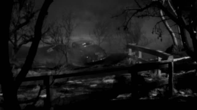a 1930s roadster turns next to a wooden fence at night. - 1930 1939点の映像素材/bロール