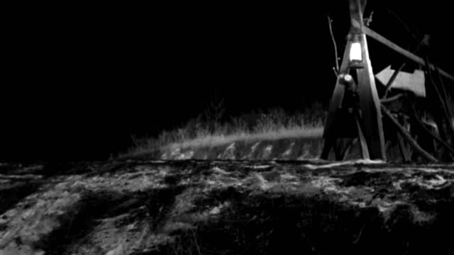 a 1930s roadster turns off a dirt road at a barricade. - 1930 1939点の映像素材/bロール
