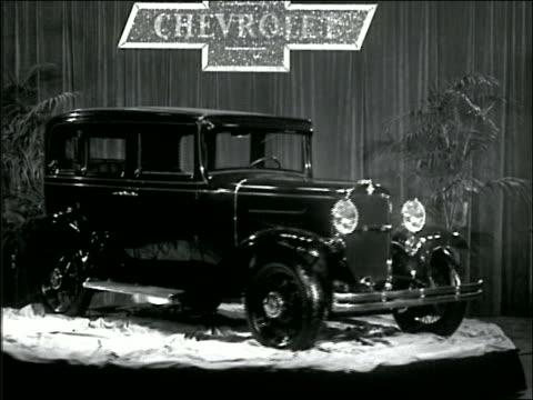 vidéos et rushes de b/w 1930s shiny black chevrolet rotating on platform in showroom - chevrolet