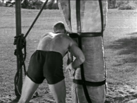 b/w 1930s shirtless football player charging tackling bag in practice / detroit lions / michigan - shirtless stock videos & royalty-free footage