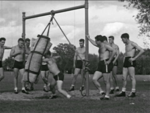 b/w 1930s shirtless football player punching bag as others watch / detroit lions practice - shirtless stock videos & royalty-free footage