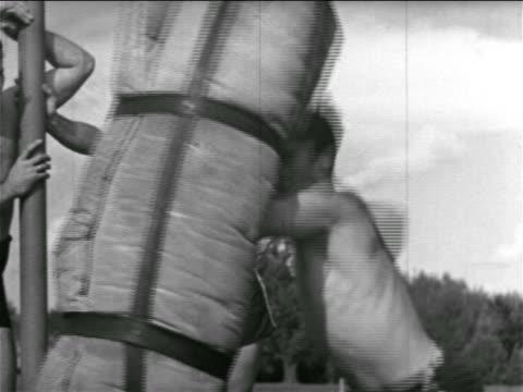b/w 1930s shirtless football player punching bag in practice / detroit lions / michigan - shirtless stock videos & royalty-free footage