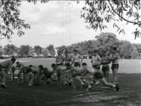 b/w 1930s shirtless football players practicing at blocking posts / michigan - shirtless stock videos & royalty-free footage