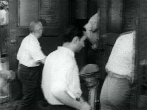 vidéos et rushes de b/w 1930s slight pan men in white shirts entering two doors of building / great depression - seulement des hommes d'âge mûr