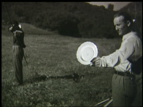 b/w 1930s slow motion man holds up plate while other shoots arrow thru it - 1935 stock-videos und b-roll-filmmaterial