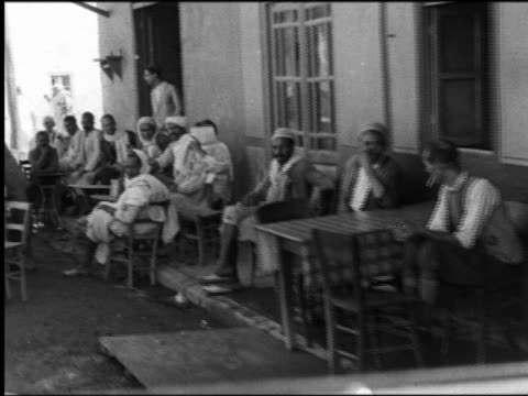 B/W 1930s slow point of view past serious men in robes + turbans sitting at tables at outdoor cafe / Kairouan, Tunisia