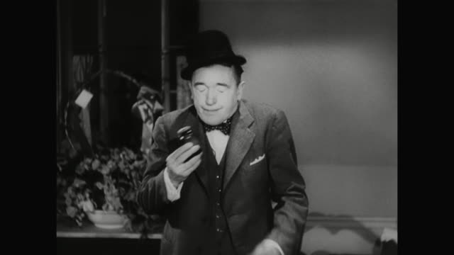 1930s smelling salts cause laurel's hat to pop off of his head - 1930 1939点の映像素材/bロール