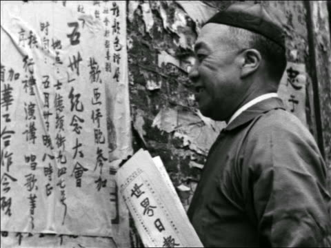 vídeos y material grabado en eventos de stock de b/w 1930s smiling man reading chinese news posted on wall / chinatown, san francisco / travelogue - only mature men