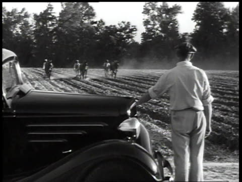 1930s WS supervisor watching workers plowing with horses / United States
