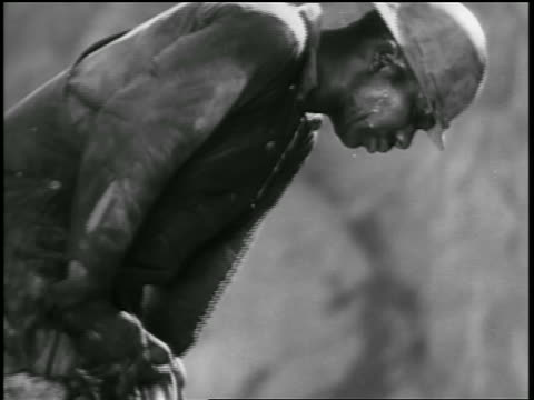 B/W 1930s sweating Black man using jackhammer in dam construction / documentary